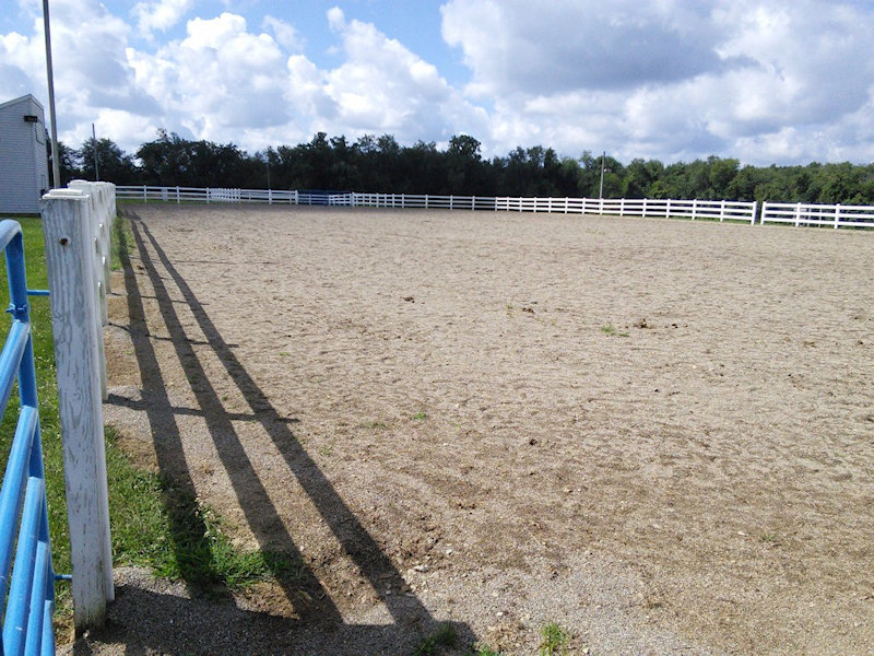 A large dirt field surrounded by white fencing