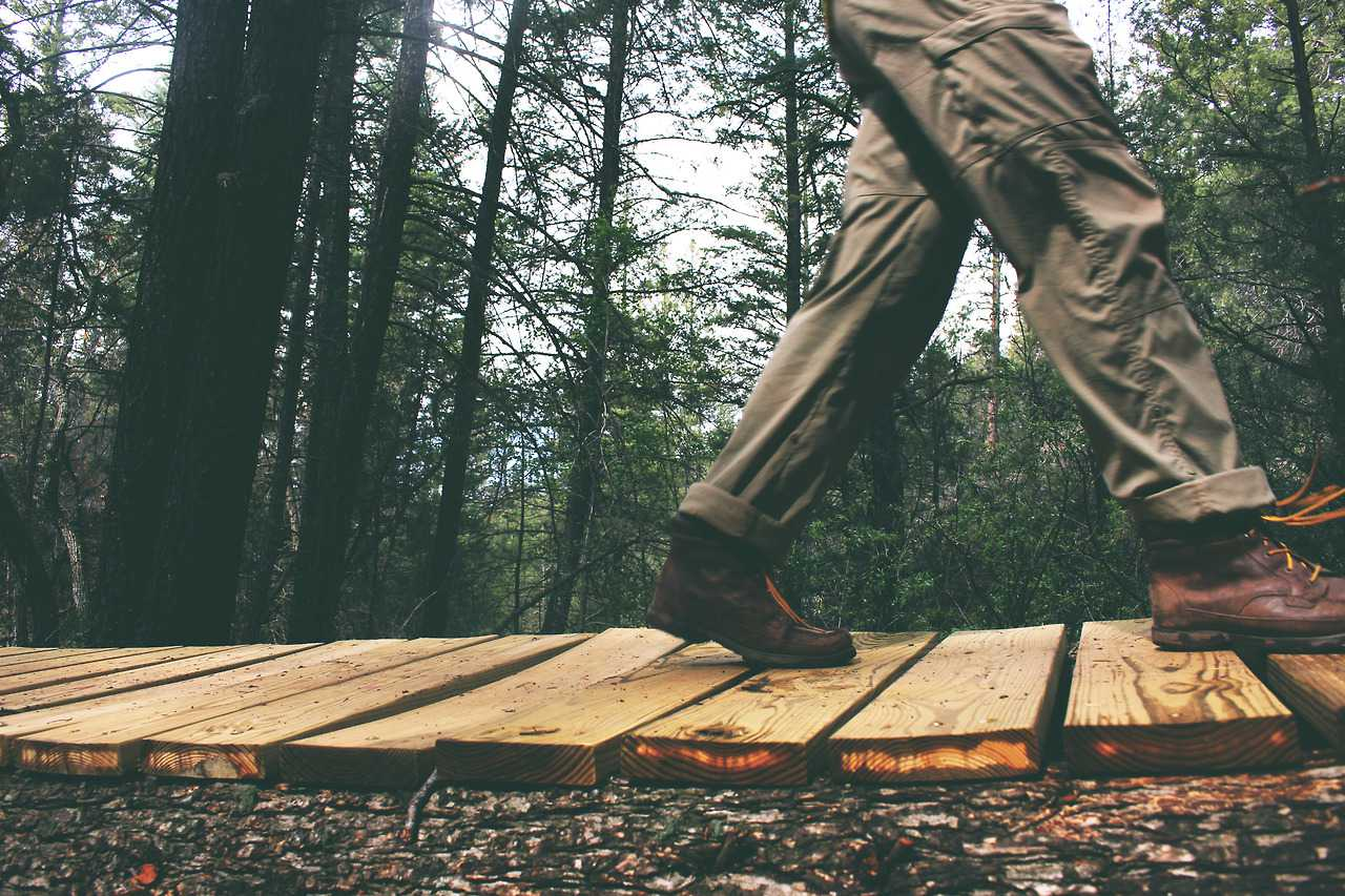 An individual walking upon a wooden trail in the woods