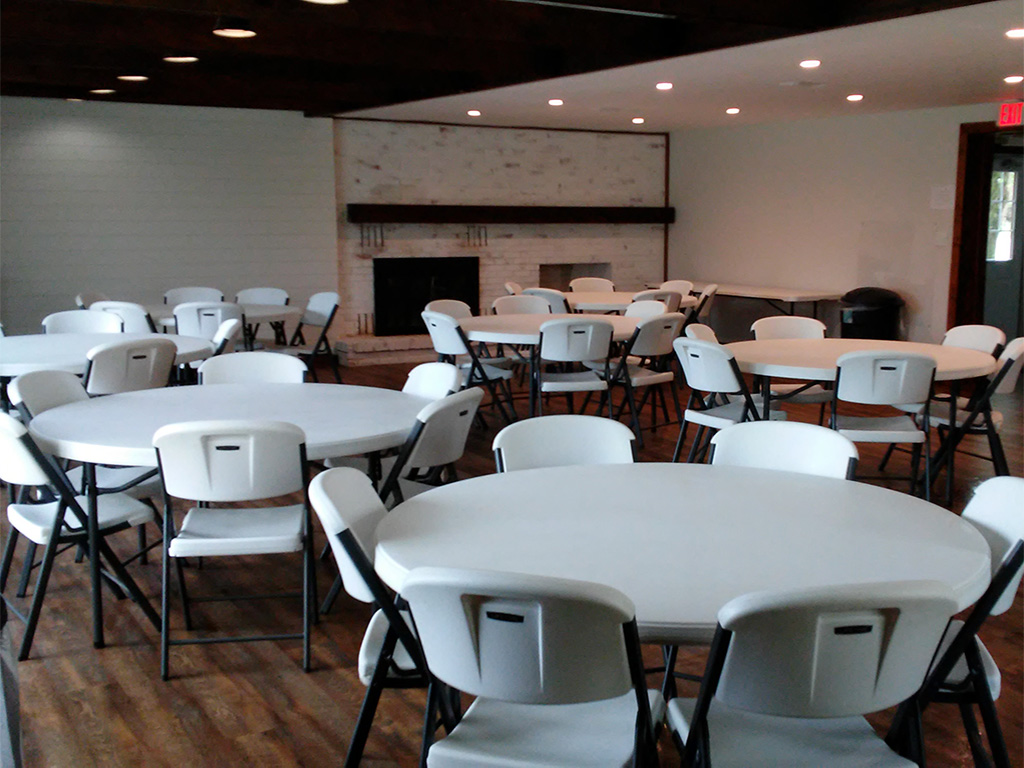 A dining area full of white circular tables and chairs